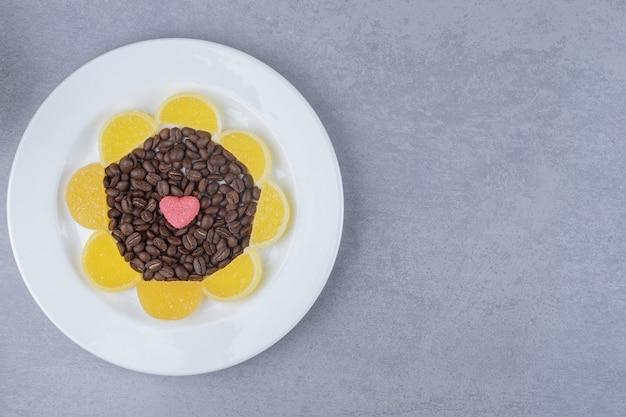 大理石の表面の大皿にコーヒー豆とマーマレードの山
