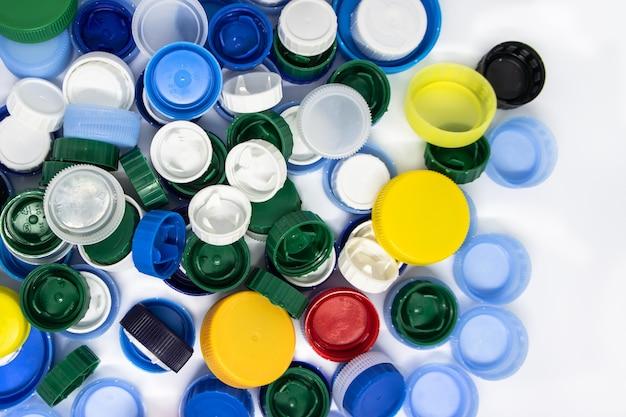 白い背景の上の色付きのプラスチックキャップの山リサイクルの概念