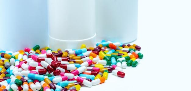 ぼやけたプラスチック製の薬瓶にカラフルな抗生物質カプセル錠剤の山。