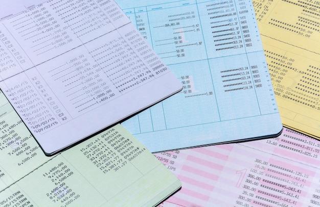 背景、口座と貯蓄の概念のためのカラフルな銀行口座の通帳の山