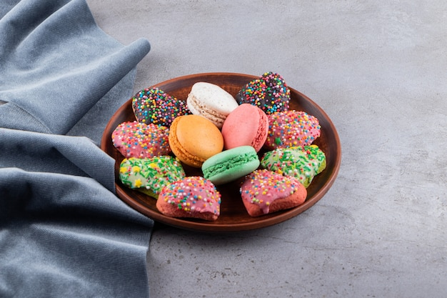 Куча красочных печений на деревянной тарелке на сером фоне.
