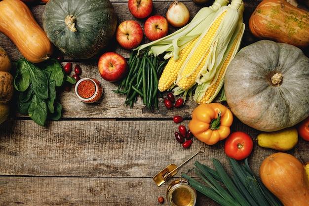 木製の背景の上面図にカラフルな果物や野菜の山