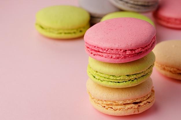 Куча красочных миндального печенья на розовом фоне