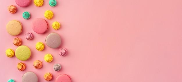 Куча красочных миндального печенья на розовом, баннерном фоне, плоской планировке
