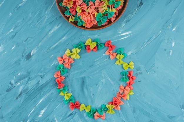 Куча красочных сырых макарон фарфалле на синей поверхности