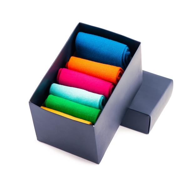 Куча красочных носков в коробке на белом фоне