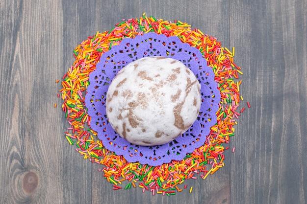 甘いクッキーの周りにカラフルなスプリンクルの山
