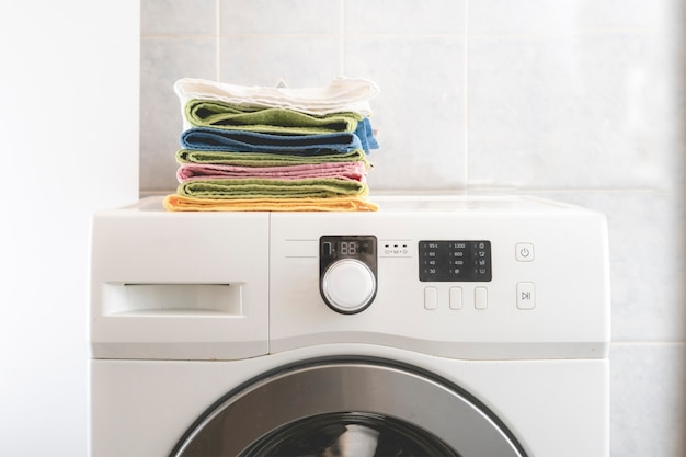 Куча разноцветных полотенец лежала в прачечной на стиральной машине и на столе b