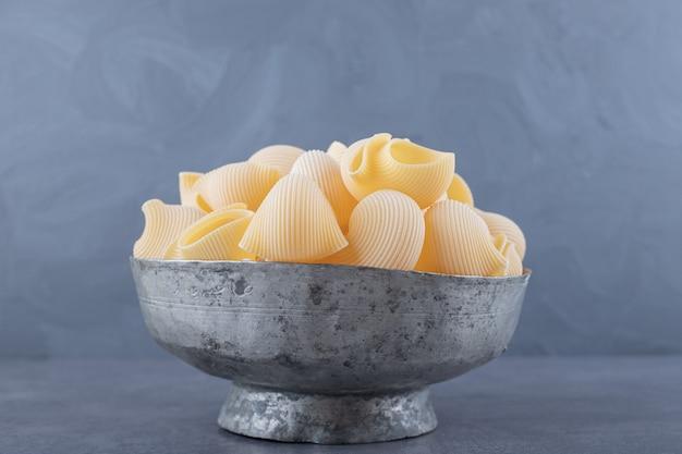 Куча макаронных изделий conchiglie в классической кружке.