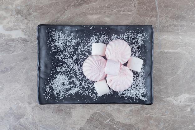 Куча печенья и зефира на блюде на мраморной поверхности