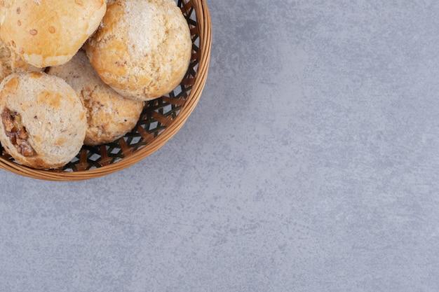 大理石の表面のバスケットにクッキーの山