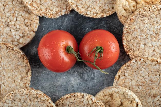Куча хрустящих хлебцев и свежих помидоров на мраморной поверхности