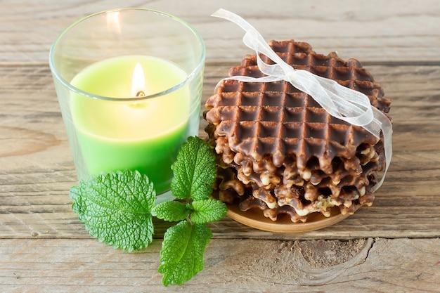木製のテーブルにミントとキャンドルを添えたおいしいチョコレートベルギーワッフルの山。