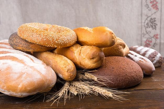 さまざまな種類の焼きたてのパン、バゲット、ベーグル、ロールパンを木のテーブルの上の全粒小麦の茎の上に積み上げます