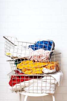 바구니에 더러운 다채로운 세탁 더미