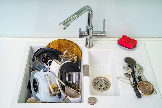 Куча грязной посуды в раковине. тарелки нуждаются в мытье. кухонная мойка с грязными тарелками.