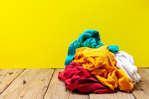 木の板の黄色の背景に汚れた洗濯物の山。
