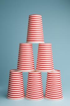 青い背景の上の使い捨てパーティーカップの山