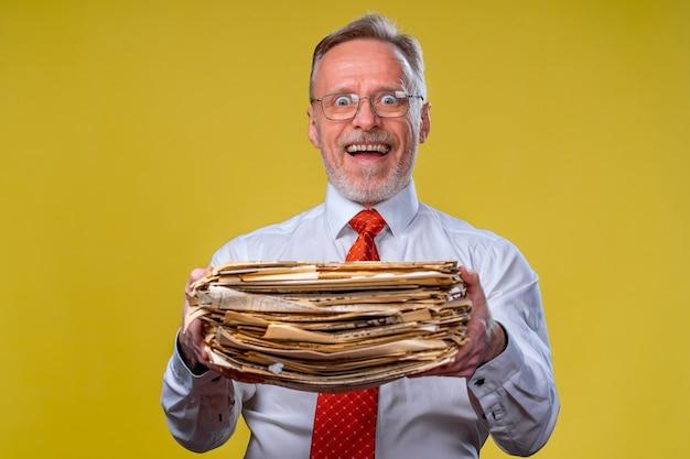 手にドキュメントの山。年配の男性は、書類の山を保持します。ハードメンタルワークに驚いた
