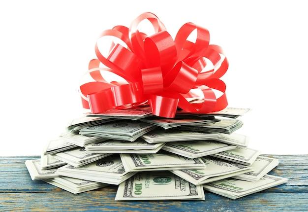 흰색 표면에 고립 된 선물로 활과 달러의 더미