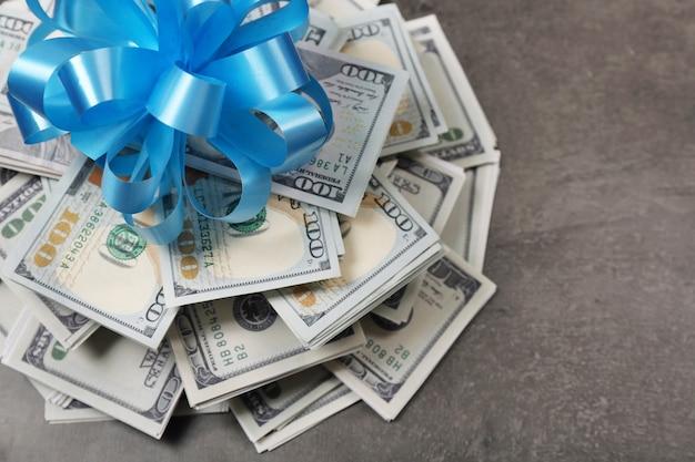 Куча долларов с бантом в подарок на сером текстурированном фоне