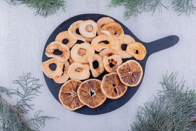 Куча сушеных яблок и дольки апельсина на небольшом подносе на белом фоне.