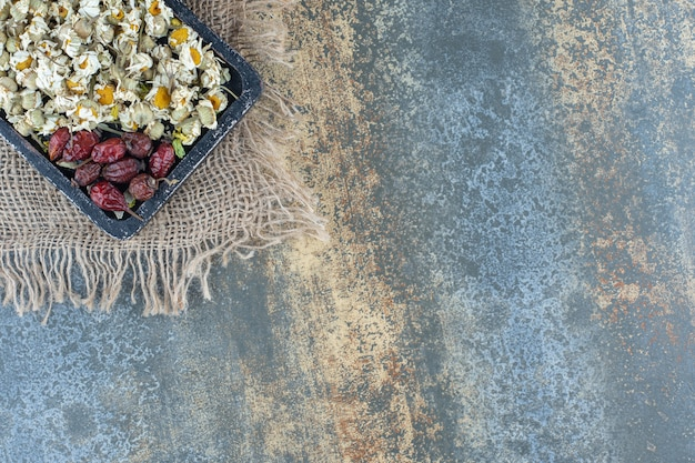 Куча сушеной ромашки и плодов шиповника на черной доске.