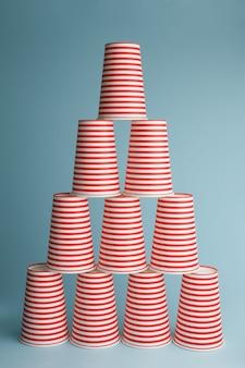 青い背景の上の飲酒パーティーカップの山