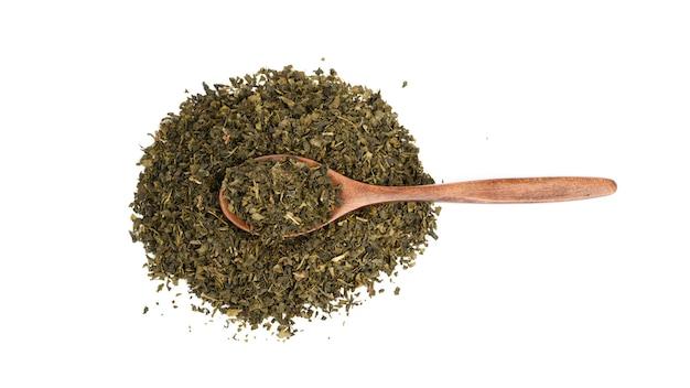 Куча сухого зеленого чая и коричневой деревянной ложкой, изолированные на белой поверхности, вид сверху