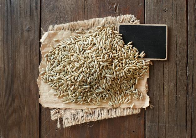 Куча сухого сырого ржаного зерна с видом сверху небольшой доске