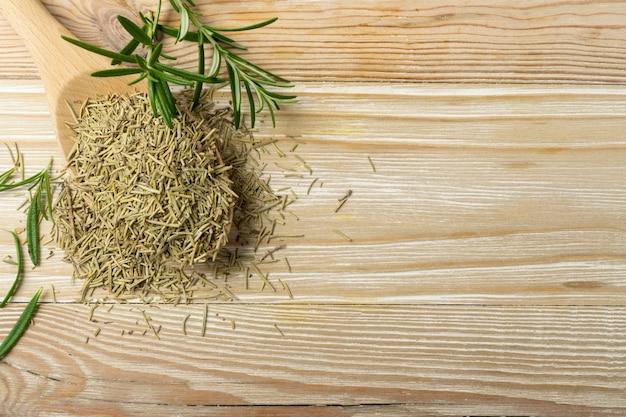 Куча сухих игл розмарина в деревянной ложке. сушеные измельченные и свежие зеленые листья розмарина вид сверху. молотые приправы, травы и специи на деревянном столе