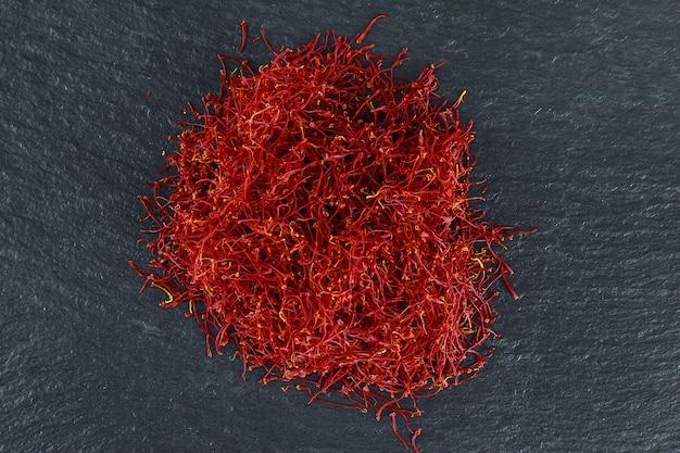 黒のテクスチャ背景に乾いたサフラン糸の山。スパイス。医学、料理、美容におけるサフランの使用。