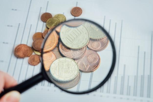 Куча монет евроцентов через увеличительное стекло на фоне графических диаграмм