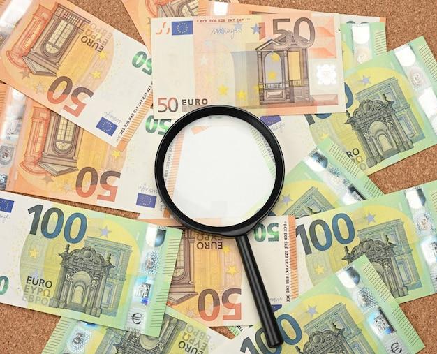 Куча евро бумажных банкнот и черная пластиковая лупа, вид сверху