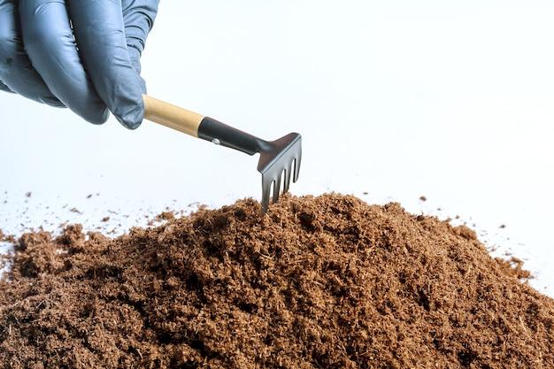 흰색 바탕에 비옥 한 토양의 더미입니다. 정원 도구. 소프트 포커스. 프리미엄 사진