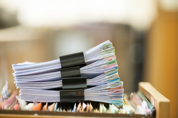 나무 책상에 화려한 클립이 있는 재무 문서 더미