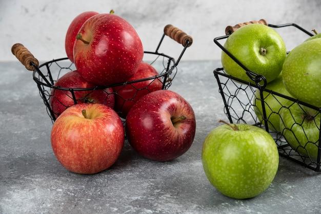 금속 바구니에 놓인 신선한 녹색 및 빨강 사과 더미.