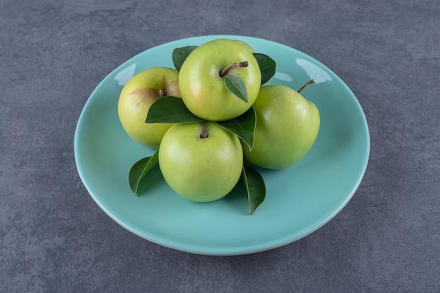 파란색 접시에 신선한 녹색 사과 더미입니다.