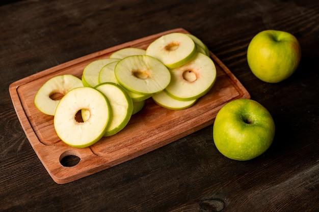 나무 커팅 보드에 있는 과일 건조기에 놓을 준비가 된 신선한 녹색 사과 더미와 식탁 근처에 있는 두 명의 할머니 스미스