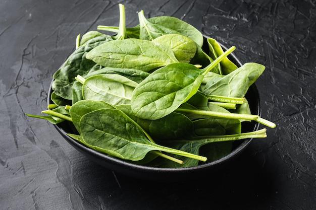 신선한 녹색 아기 시금치 잎 더미, 그릇에, 검은 돌 배경에