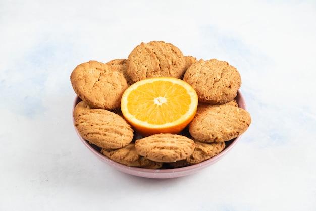 그릇에 오렌지와 신선한 수 제 쿠키의 더미.