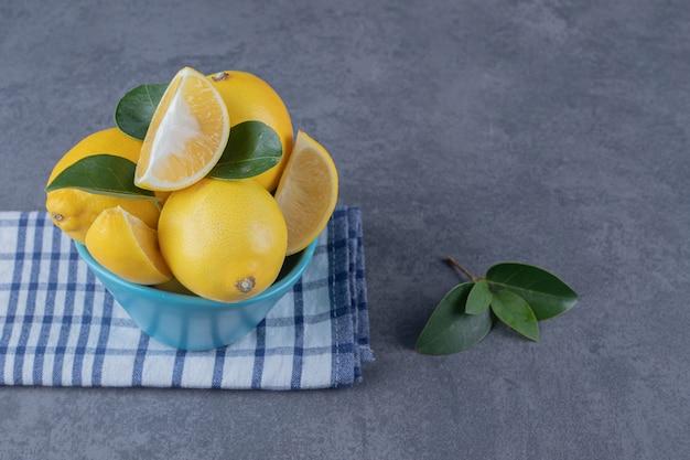 파란색 그릇에 신선한 레몬 더미입니다.