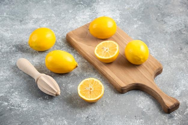 신선한 레몬 더미 전체 또는 절반 잘라.