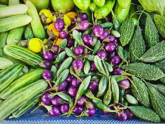 市場の屋台で販売されている新鮮な紫色のナスきゅうりやその他の果物の山