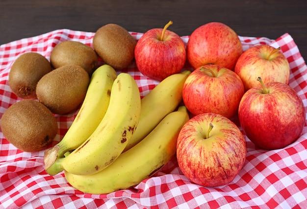 Куча свежих спелых фруктов ассорти на клетчатой скатерти для концепции здоровья