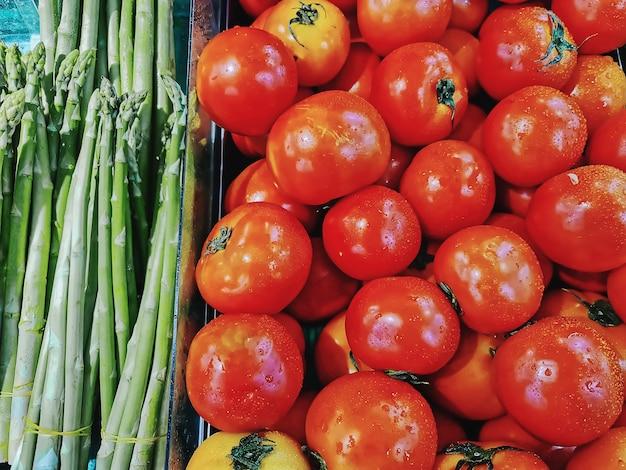 Куча свежих помидоров и спаржи для продажи на рыночных прилавках