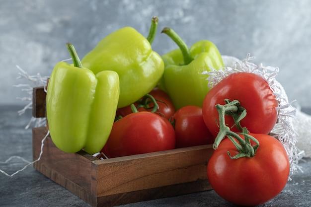 Куча свежих овощей на деревянной корзине на сером фоне.