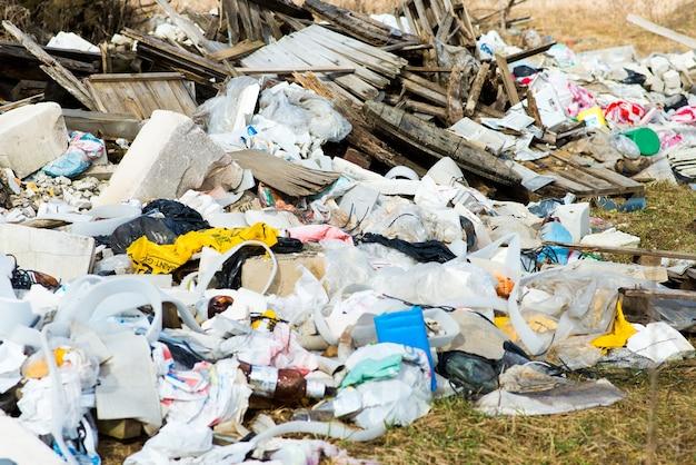 Куча мусорной свалки в лесу. проблемы окружающей среды природы. загрязненная природа лесов.