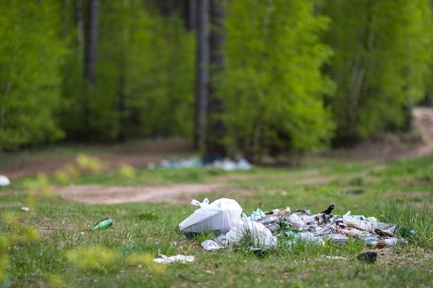 自然環境問題における緑の草の上のゴミの山