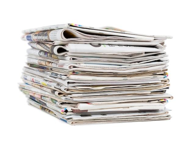 白い背景のクローズアップショットで分離された一般的な新聞の山。ニュースとアップデートのコンセプト。